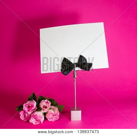 Note holder with the male butterfly with rose and empty card on a crimson background