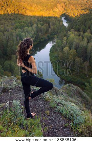 Young beautiful woman doing yoga outdoors
