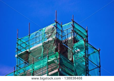 scaffolding of iron pipes and green network used for the restoration of ancient buildings and records