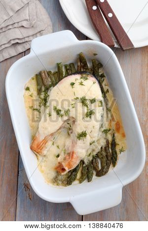 Salmon and asparagus under Bechamel sauce in a baking dish