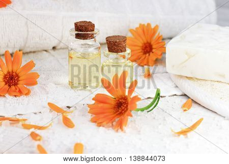 Aroma essential oil of calendula, golden infusion in bottles. Fresh marigold flowers, white towel, sea salt and orange petals scattered.