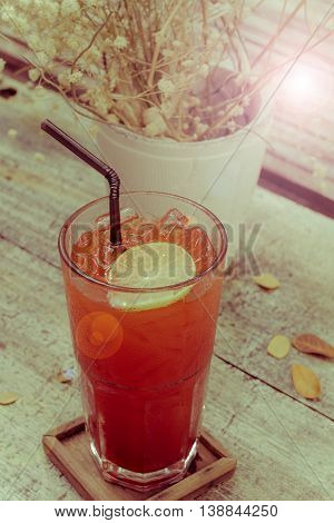Summer lemon ice tea on the table with dry leaves. Vintage retro style