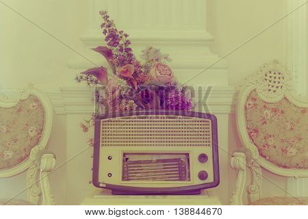antique radio with flower and chairs on vintage background.