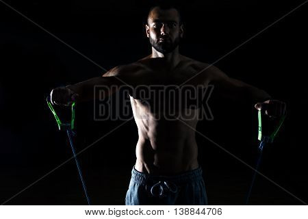 Muscular Man Skipping Rope. Portrait Of Muscular Young Man Exercising With Jumping Rope On Black Bac