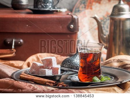 Turkish tea in traditional glass cup with turkish delight