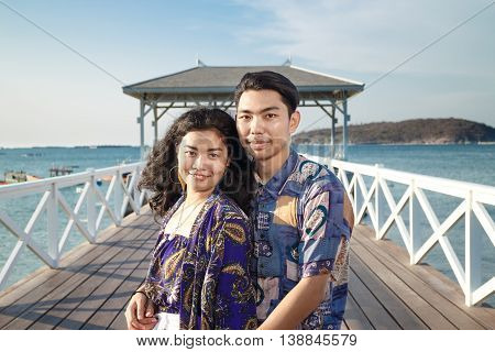 asian couple woman long black hair with blue shawl and white jeans and man short hair with blue shirt standing at wood bridge Asdang in SICHANG island Thailand landmark