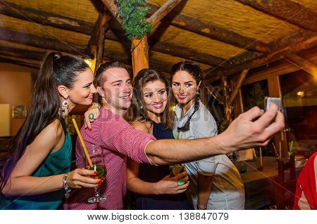 Young beautiful people with cocktails in bar or club taking selfie, having fun