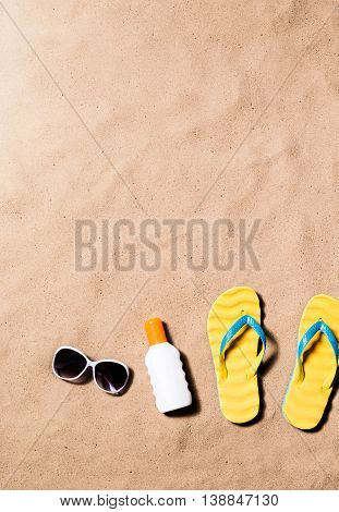 Summer vacation composition with a pair of yellow flip flop sandals, sunglasses and suntan cream on a beach. Sand beach background, studio shot, flat lay. Copy space.