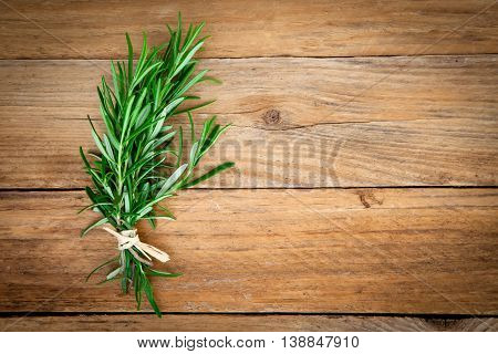 green rosemary bound on a wooden background.