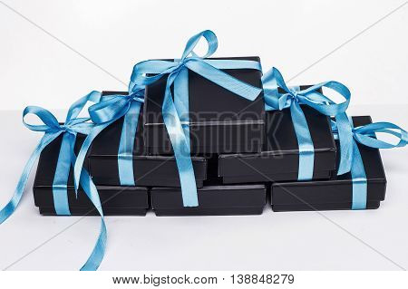 A beautiful pyramid of black boxes with blue bows on a white background