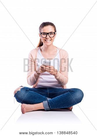 Teenage girl in white t-shirt, pink cardigan, jeans and trendy black eyeglasses, holding a smart phone, texting, sitting on the floor, young beautiful woman, studio shot on white background, isolated