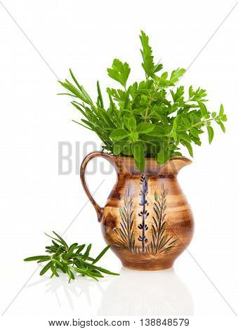 rosemary oregano and parsley in a jar on white background.