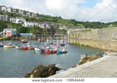 Mevagissey Cornwall United Kingdom - July 02 2016: Harbour of small Cornish fishing village with houses in background