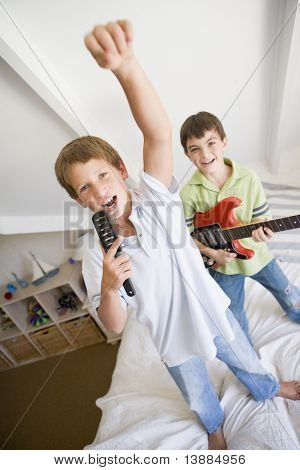 Two Boys Standing On A Bed, Playing Guitar And Singing Into A Hairbrush