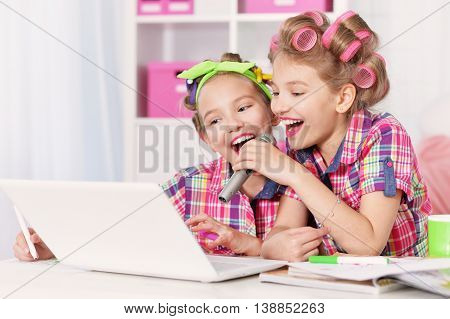 Cute  tweenie girls  in hair curlers  with laptop , singing in karaoke at home