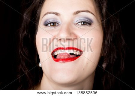 Close-up woman looks straight into the camera on a black background. expresses different emotions, showing tongue.