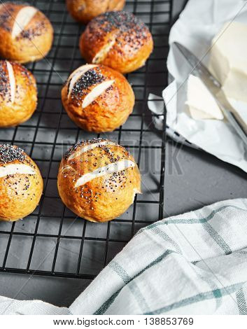 Homemade baked golden pretzel buns with poppy seeds with buuter near it on stone background. Pretzel bun is german cuisine dish, ideal for lunch or breakfest with butter and tea.