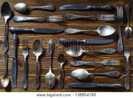 Old used cutlery on rustic wooden background, flat lay.