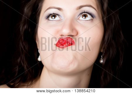 Close-up woman looks straight into the camera on a black background. expresses different emotions, sending a kiss.