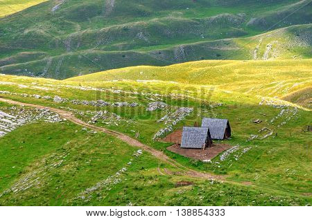 Montenegro national park Durmitor houses mountains and clouds panorama. Sunlight lanscape. Nature travel background