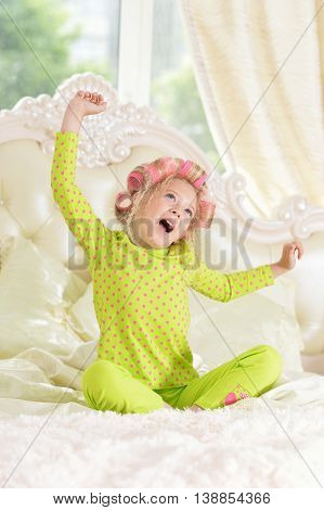Happy cute little girl in hair curlers awaked up