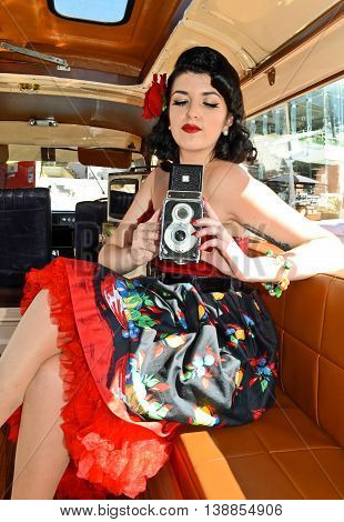 Retro girl with twin lens camera at retro fashion and classic car show in Auckland, New Zealand