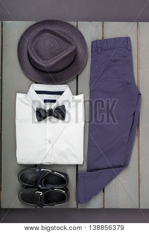 Men's Outfit On Wooden Background. Kids Fashion Clothes. Grey Fedora, Navy Pant, White Shirt, Black