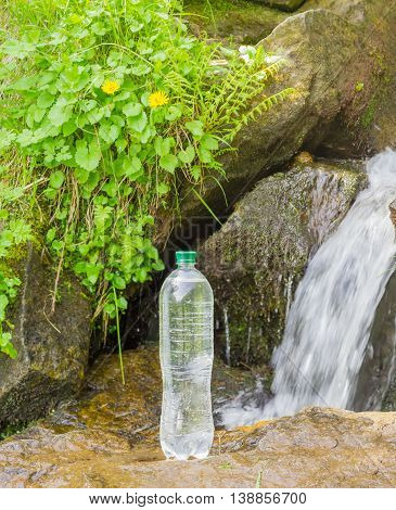 Plastic bottle of drinking water on wet stone on the background of a small waterfall on the mountain stream