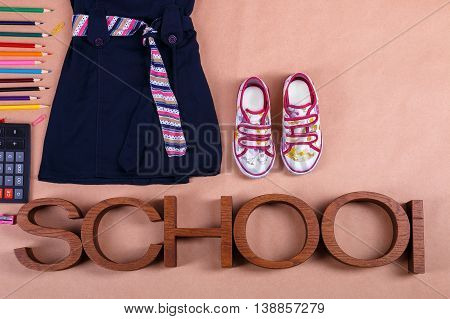 School uniform near sneakers and school supplies on orange background with an inscription school. Top view, Copy space.  outfit. Back to school.