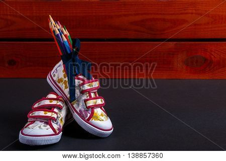 Set of colored pencils wrapped in a blue ribbon near sneakers on black wooden background. Back to school.