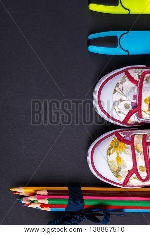 Set of colored pencils wrapped in a blue ribbon near sneakers and marker on black wooden background. Back to school.