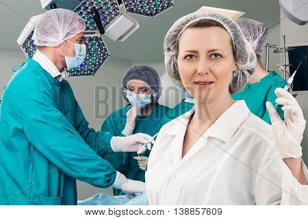 Adult female anesthetist with syringe on the surgery teem background
