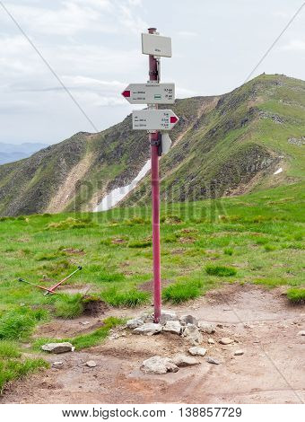 Signpost of hiking trails indicating the direction distance and time on the background of mountain peak and sky