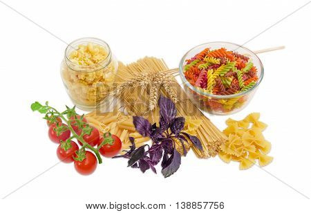 Uncooked dried long pasta two varieties colored spiral pasta penne creste di galli and farfalle pasta several wheat spikes sprigs of basil and cluster of cherry tomatoes on a light background