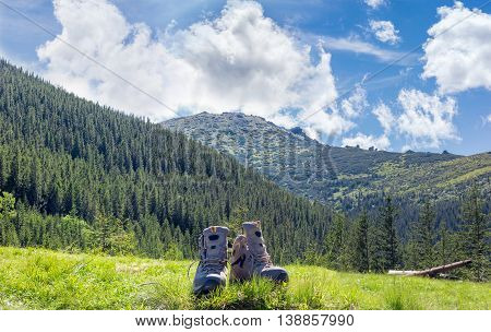 Pair of leather light brown trekking shoes in a clearing in the grass against the backdrop of mountain slopes covered with fir forest and sky with clouds