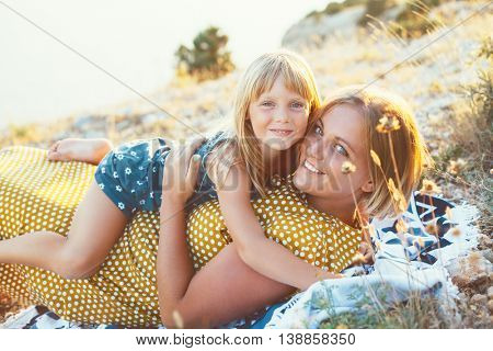 Mom playing with her child on top of the mountain in sunlight, daughter hugging mama