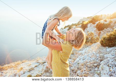 Mom playing with her child on top of the mountain in sunlight