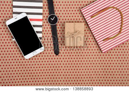 Shopping Bag, Gift Box, Notepad, Watch And Smart Phone On Craft Paper Background In Red Polka Dots