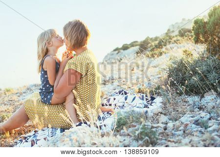 Mom playing with her child on top of the mountain in sunlight, daughter kissing mama