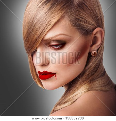 Portrait of young vampire sexy woman with red lipstick over gray background