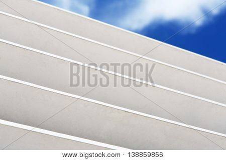 White wooden louver window fragment with sky visible outside. Modern interior details background. Contemporary architecture elements, blue sky and clouds visible through stripes.
