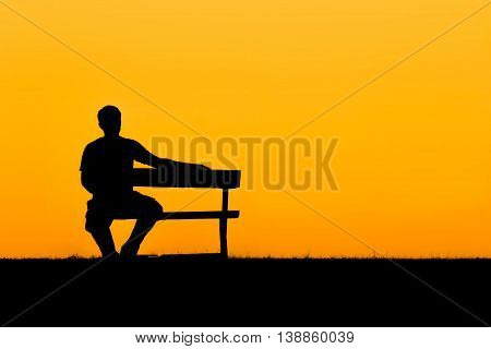 A silhouette of man sitting on bench and him looking at the sky in sunset