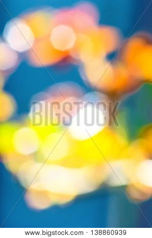 Abstract blue background with blurry yellow orange white green spots
