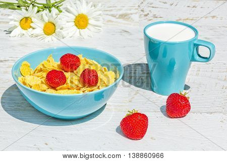 Breakfast in the garden on a sunny summer day. Bowl with corn flakes and strawberry mug with milk on a background white wooden table and a bouquet of daisies