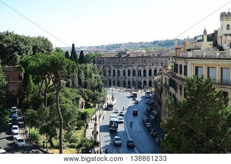 Rome Italy 18 June 2016. Theater of Marcellus view from Capitol Hill. The street named by the theater Via del Teatro di Marcello with tourists, traffic and public buses.