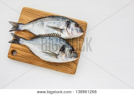 Two Fresh Dorado Fish On Wooden Cutting Board. Top View, Copy Space.