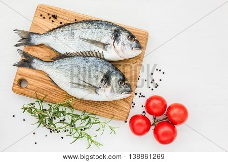 Fresh Dorado Fish On Wooden Cutting Board With Tomatoes On White Table. Top View, Copy Space.