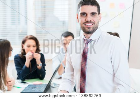 Man and group having business meeting in office