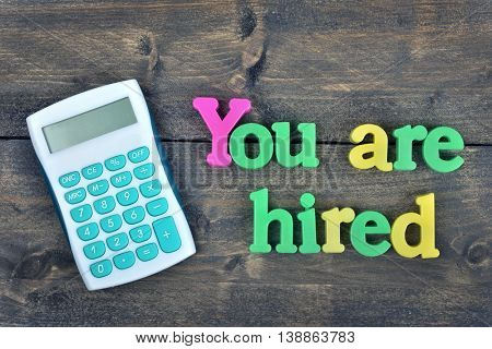 You are hired word on wooden table