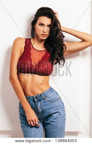 portrait of a beautiful brunette in a sexy bra and jeans beautiful makeup and hairstyle